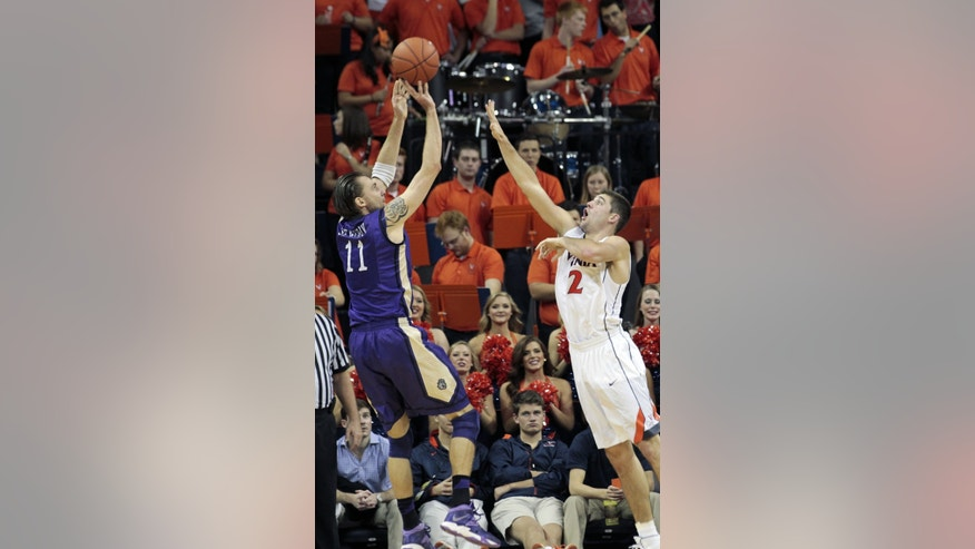 James Madison forward Andrey Semenov (11) shoots over Virginia guard Joe Harris (12) during the second half of an NCAA college basketball game on Friday, Nov. 8, 2013, in Charlottesville, Va. (AP Photo/Ryan M. Kelly)