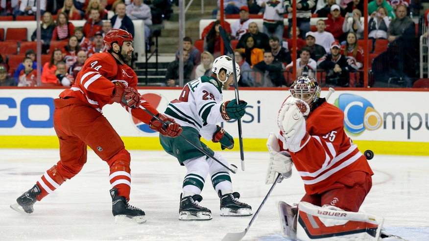 Carolina Hurricanes' Jay Harrison (44) defends as Minnesota Wild's Jason Pominville (29) scores on Hurricanes goalie Justin Peters (35) during the first period of an NHL hockey game in Raleigh, N.C., Saturday, Nov. 9, 2013. (AP Photo/Gerry Broome)