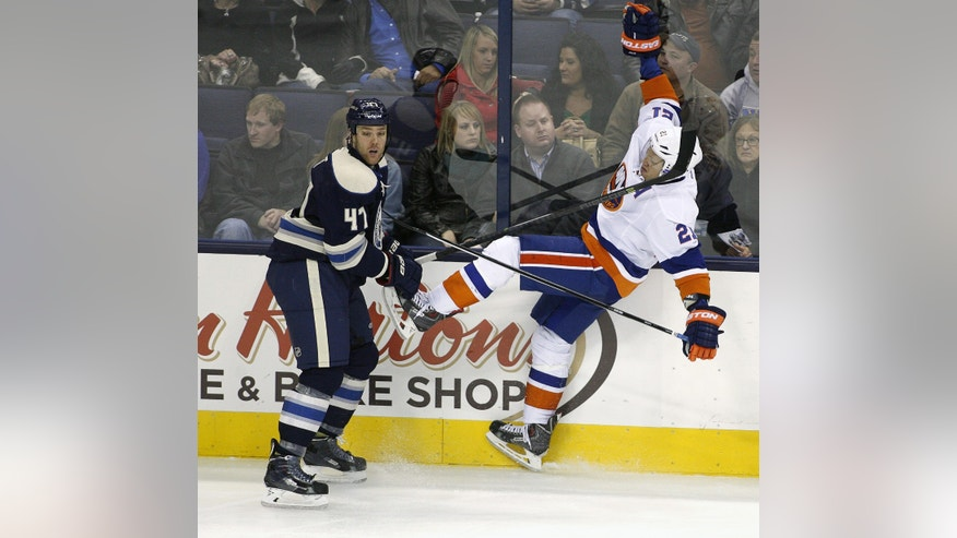 New York Islanders' Kyle Okposo (21) falls back after colliding with Columbus' Dalton Prout (47) during the third period of an NHL hockey game Saturday, Nov. 9, 2013, in Columbus, Ohio. (AP Photo/Mike Munden)
