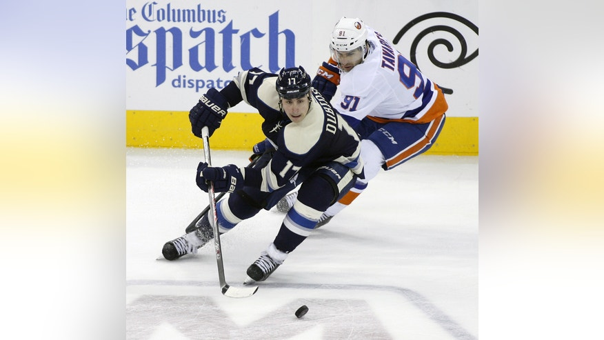 Columbus' Brandon Dubinsky (17) keeps the puck away from New York Islanders' John Tavares (91) during the third period of an NHL hockey game Saturday, Nov. 9, 2013, in Columbus, Ohio. Columbus won 5-2. (AP Photo/Mike Munden)