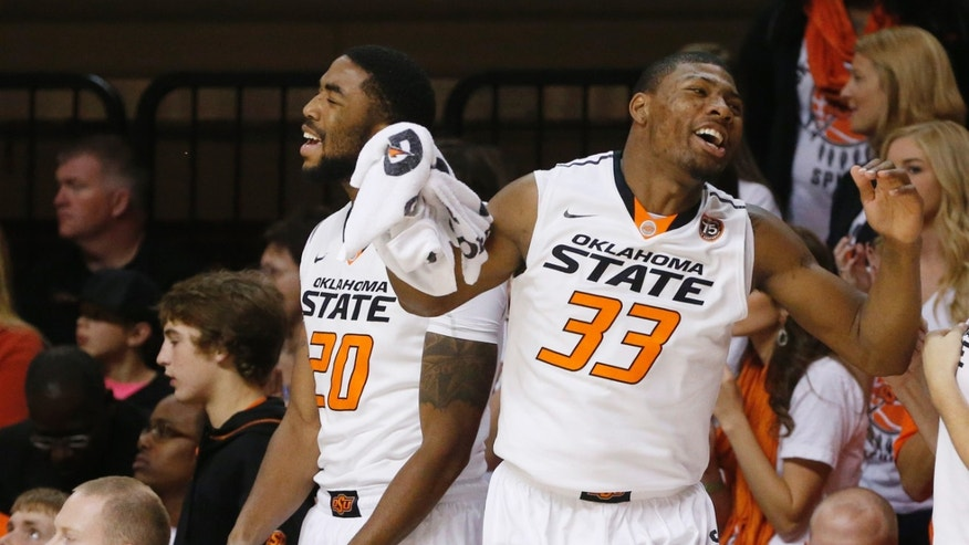 Oklahoma State post Michael Cobbins (20) and guard Marcus Smart (33) react to a basket by teammate Markel Brown in the first half of an NCAA college basketball game against Mississippi Valley State in Stillwater, Okla., Friday, Nov. 8, 2013. (AP Photo/Sue Ogrocki)