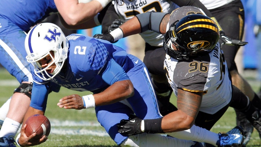 Kentucky quarterback Jalen Whitlow (2) is sacked by Missouri's Lucas Vincent (96) during the second quarter of an NCAA college football game, Saturday, Nov. 9, 2013, in Lexington, Ky. (AP Photo/James Crisp)