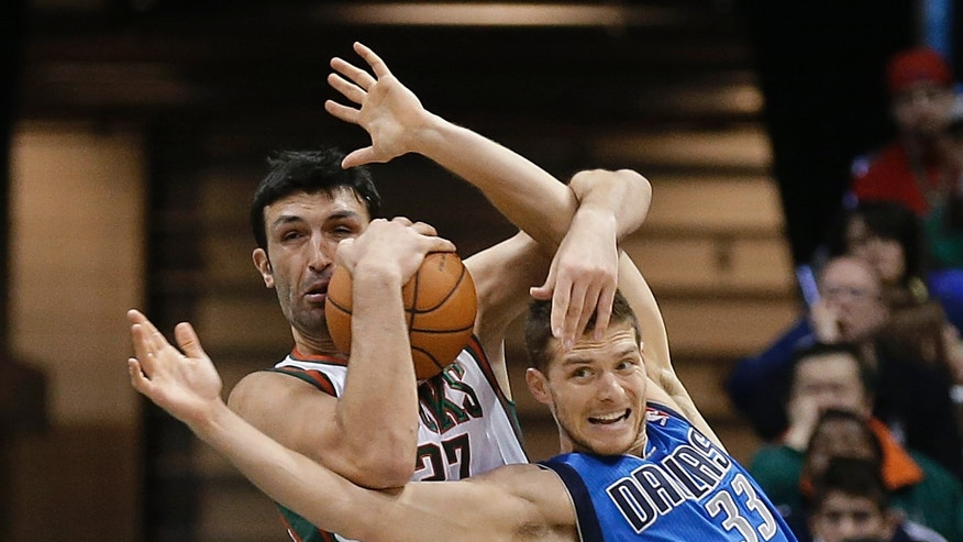 Milwaukee Bucks' Zaza Pachulia, left, wrestles a rebound away from Dallas Mavericks' Gal Mekel during the second half of an NBA basketball game Saturday, Nov. 9, 2013, in Milwaukee. (AP Photo/Jeffrey Phelps)