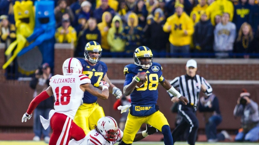Michigan quarterback Devin Gardner (98) tries to get away from Nebraska safety LeRoy Alexander (18) and defensive end Jason Ankrah (9) in the second quarter of an NCAA college football game in Ann Arbor, Mich., Saturday, Nov. 9, 2013. (AP Photo/Tony Ding)