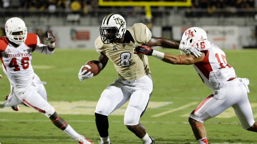 Central Florida's Storm Johnson (8) tries to get past Houston's Adrian McDonald, right, and Trevor Harris (46) during the first half of an NCAA college football game in Orlando, Fla., Saturday, Nov. 9, 2013. (AP Photo/John Raoux)