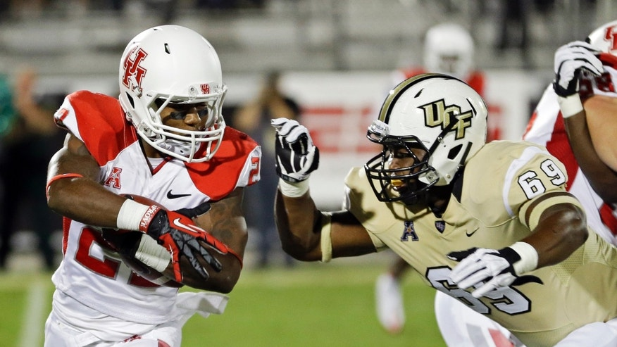 Houston running back Ryan Jackson, left, looks for a way around Central Florida's Thomas Niles (69) during the first half of an NCAA college football game in Orlando, Fla., Saturday, Nov. 9, 2013. (AP Photo/John Raoux)