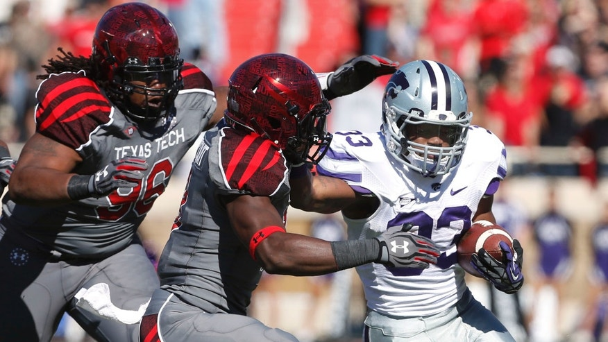 Texas Tech's Dennell Wesley, left, and Sam Eguavoen (13) try to stop Kansas State's John Hubert (33) during the first half of an NCAA college football game in Lubbock, Texas, Saturday, Nov. 9, 2013. (AP Photo/Lubbock Avalanche-Journal,Stephen Spillman) ALL LOCAL TV OUT