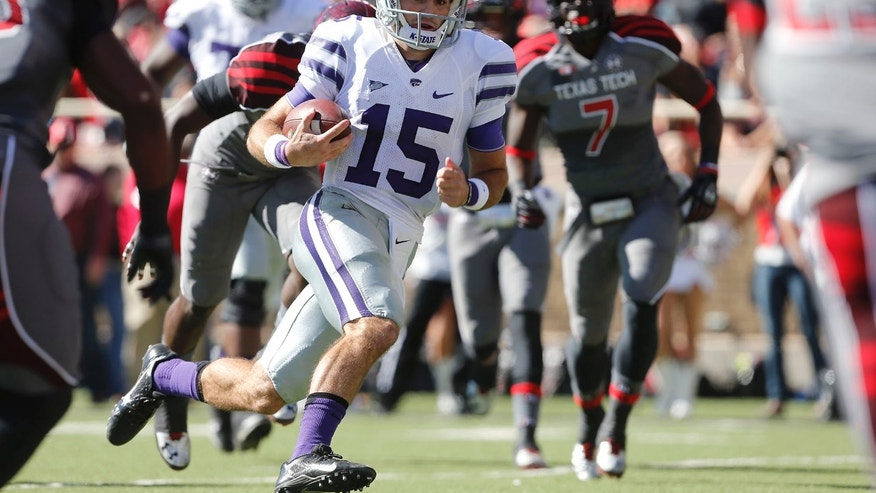 Kansas State's Jake Waters(15) looks for space as he scores a touchdown past Texas Tech's Will Smith (7) during the first half of an NCAA college football game in Lubbock, Texas, Saturday, Nov. 9, 2013. (AP Photo/Lubbock Avalanche-Journal,Stephen Spillman) ALL LOCAL TV OUT