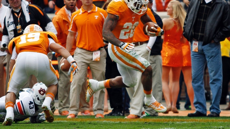 Tennessee running back Rajion Neal (20) escapes from Auburn linebacker Anthony Swain (43) to score a touchdown in the second quarter of an NCAA college football game on Saturday, Nov. 9, 2013, in Knoxville, Tenn. Tennessee receiver Devrin Young (19) blocks. (AP Photo/Wade Payne)