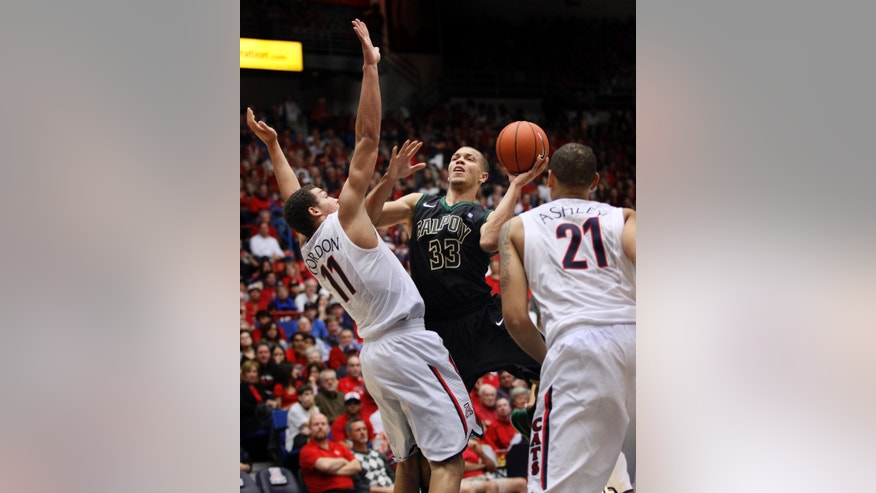 Cal Poly's Chris Eversley (33) shoots for two between Arizona's Aaron Gordon (11) and Brandon Ashley (21) in the first half of an NCAA college basketball game, Friday, Nov. 8, 2013 in Tucson, Ariz.  (AP Photo/Wily Low)