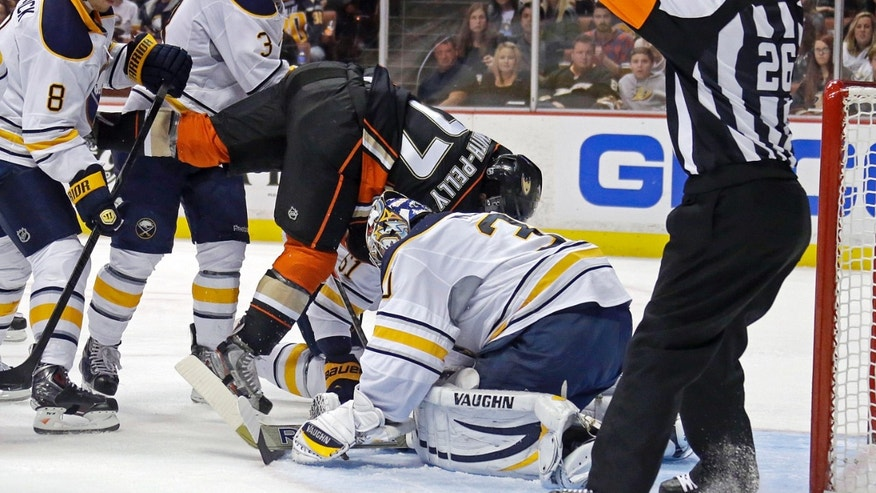 Anaheim Ducks right winger Devante Smith-Pelly (77) and Buffalo Sabres goalie Ryan Miller, second from right, tangle in the goal in the second period of an NHL hockey game in Anaheim, Calif., Friday, Nov. 8, 2013. (AP Photo/Reed Saxon)