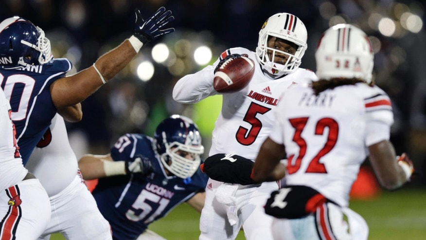 Louisville quarterback Teddy Bridgewater (5) looks to pass as he is pressured by Connecticut during the second quarter of an NCAA college football game, in East Hartford, Conn., Friday, Nov. 8, 2013. (AP Photo/Charles Krupa)