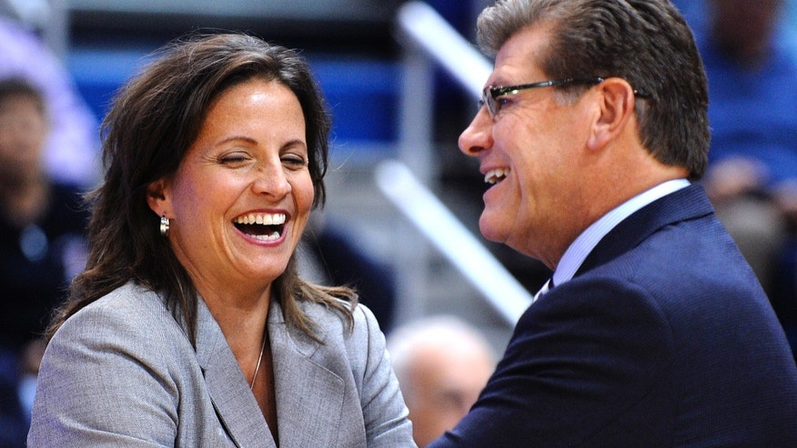 Connecticut coach Geno Auriemma speaks with Hartford coach Jennifer Rizzotti before an NCAA college basketball game in Hartford, Conn., on Saturday, Nov. 9, 2013. (AP Photo/Fred Beckham)