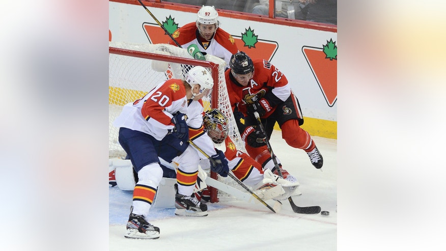 Ottawa Senators' Chris Neil, right, wraps the puck around the net as Florida Panthers' Tim Thomas reaches for hit with his glove during an NHL hockey game in Ottawa, Ontario, on Saturday, Nov. 9, 2013. (AP Photo/The Canadian Press, Sean Kilpatrick)