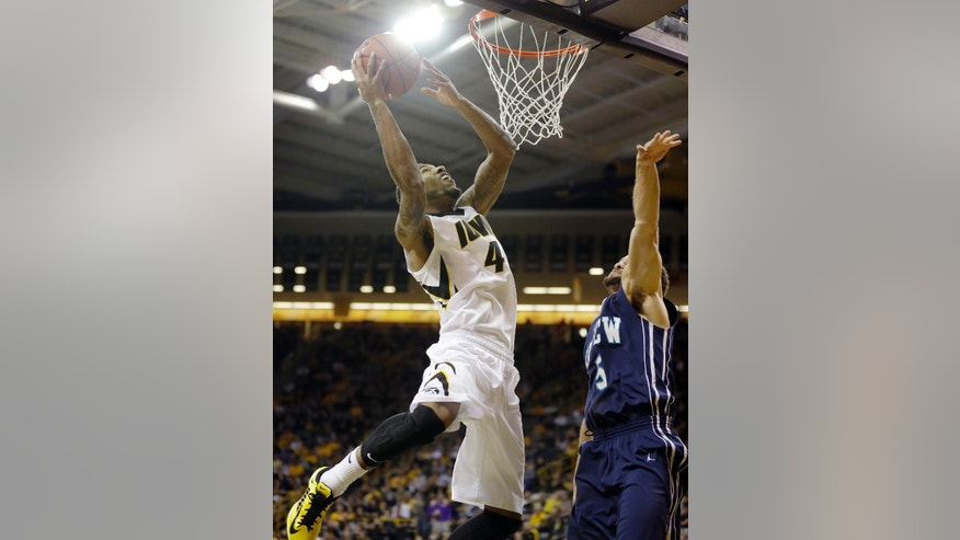 Iowa guard Devyn Marble, left, shoots over UNC-Wilmington guard Ben Eblen during the first half of an NCAA college basketball game, Friday, Nov. 8, 2013, in Iowa City, Iowa. (AP Photo/Charlie Neibergall)