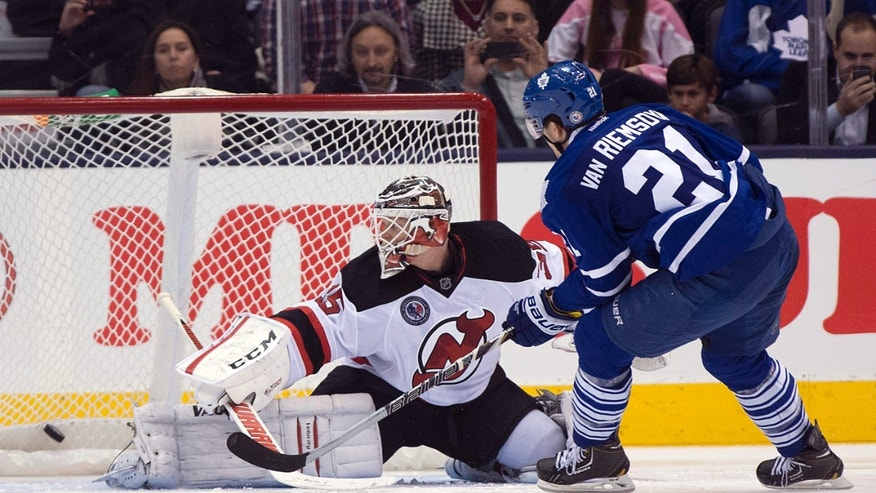 Toronto Maple Leafs left winger James van Riemsdyk scores the game winning shootout goal on New Jersey Devils goaltender Cory Schneider during an NHL hockey game, Friday, Nov. 8, 2013 in Toronto. (AP Photo/The Canadian Press, Frank Gunn)