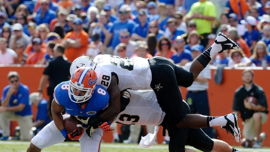Florida wide receiver Trey Burton (8) gets hit by Vanderbilt linebackers Karl Butler (28) and linebacker Jake Sealand (13) after catching a pass during the second half of an NCAA college football game Saturday, Nov. 9, 2013 in Gainesville, Fla. (AP Photo/Phil Sandlin)