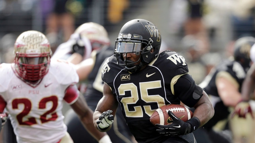Wake Forest tailback Josh Harris (25) carries the ball as Florida State linebacker Telvin Smith pursues him in the first half of an NCAA college football game in Winston-Salem, N.C., Saturday, Nov. 9, 2013. (AP Photo/Nell Redmond)