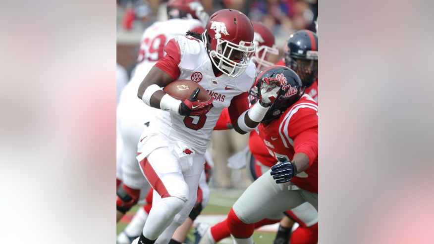Arkansas running back Alex Collins (3) runs upfield for short yardage against Mississippi defenders during the first half of an NCAA college football game at Vaught-Hemingway Stadium in Oxford, Miss., on Saturday, Nov. 9, 2013. (AP Photo/Rogelio V. Solis)