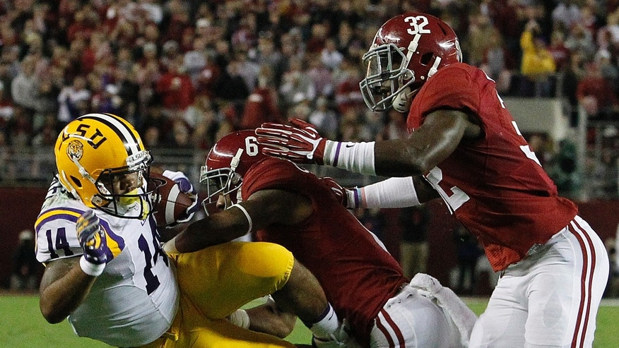 LSU running back Terrence Magee (14) is hit by Alabama defensive back Ha Ha Clinton-Dix (6) and Alabama linebacker C.J. Mosley (32) during the first half of an NCAA college football game, Saturday, Nov. 9, 2013, in Tuscaloosa, Ala. (AP Photo/Butch Dill)