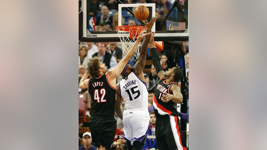 Sacramento Kings center DeMarcus Cousins, center, goes to the basket between Portland Trail Blazers' Robin Lopez, left, and LaMarcus Aldridge during the first quarter of an NBA basketball game in Sacramento, Calif., Saturday, Nov. 9, 2013. (AP Photo/Rich Pedroncelli)