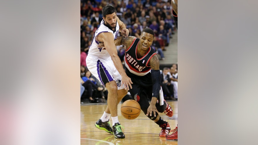 Sacramento Kings guard Greivis Vasquez, left, of Venezuela, tries to steal the ball from Portland Trail Blazers guard Damian Lillard during the first quarter of an NBA basketball game in Sacramento, Calif., Saturday, Nov. 9, 2013. (AP Photo/Rich Pedroncelli)