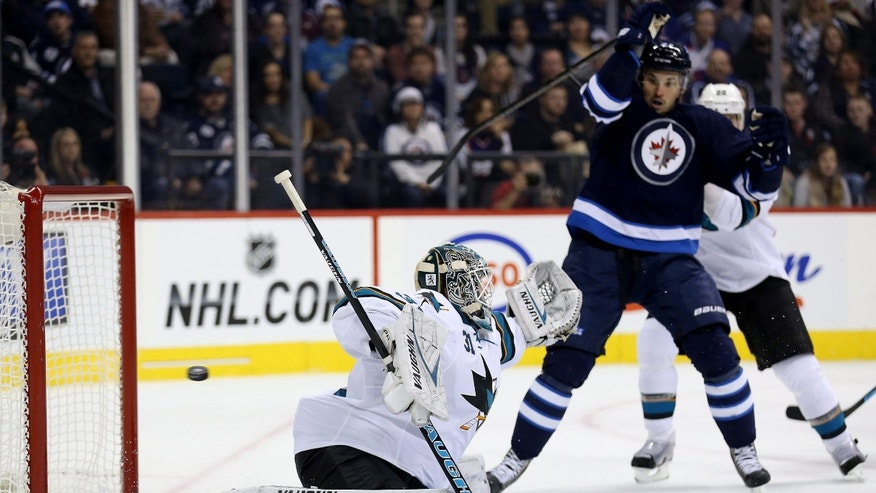 San Jose Sharks' goaltender Antti Niemi (31) with Winnipeg Jets' Eric Tangradi (27) on the doorstep fails to stop the shot by Jets Dustin Byfuglien during second period NHL hockey action in Winnipeg, Manitoba, Sunday, Nov.10, 2013. (AP Photo/The Canadian Press, Trevor Hagan)
