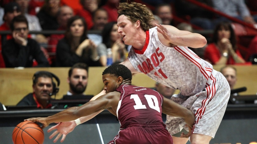 New Mexico's Cameron Bairstow, right, defends Alabama A&M's Jeremy Crutcher during the first hall of an NCAA college basketball game in Albuquerque, N.M., Saturday, Nov. 9, 2013. (AP Photo/Eric Draper)
