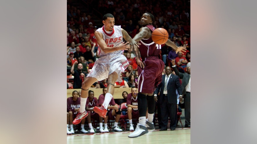 New Mexico's Kendall Williams passes the ball around Alabama A&M's Rakia Battle in the first half of an NCAA college basketball game in Albuquerque, N.M., Saturday, Nov. 9, 2013. (AP Photo/Eric Draper)
