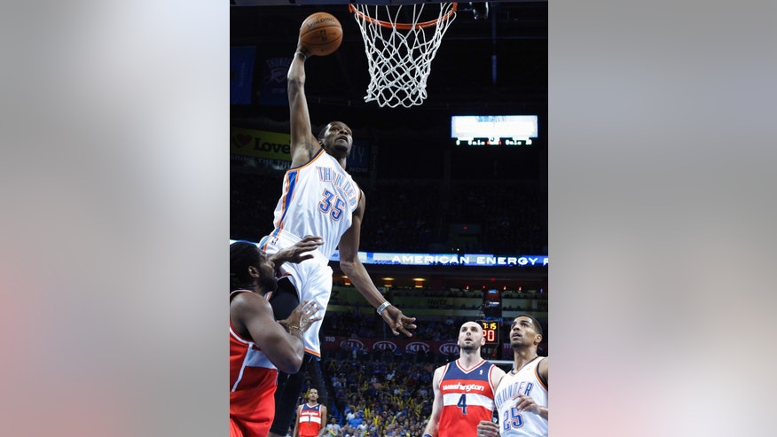 Oklahoma City Thunder forward Kevin Durant (35) goes up for a dunk in front of Washington Wizards forward Nene, left, and center Marcin Gortat (4) in the first quarter of an NBA basketball game in Oklahoma City, Sunday, Nov. 10, 2013. (AP Photo/Sue Ogrocki)