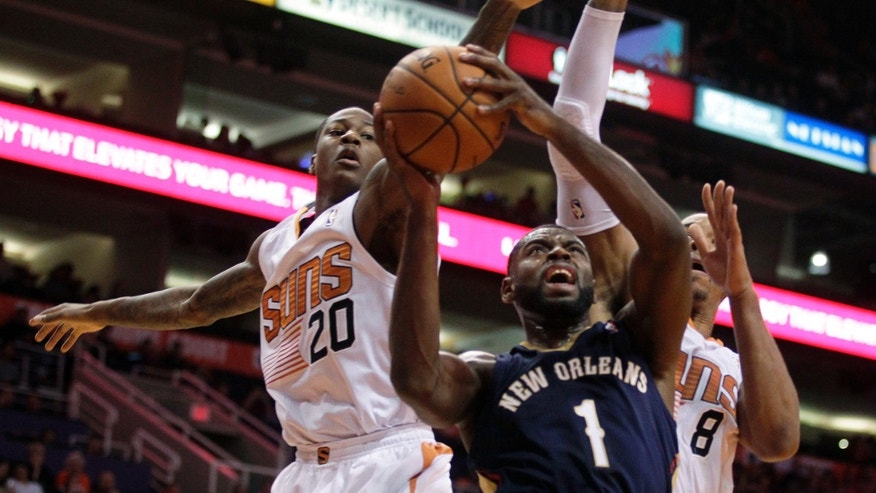 New Orleans Pelicans point guard Tyreke Evans (1) drives between Phoenix Suns shooting guard Archie Goodwin (20) and forward Channing Frye (8) in the second quarter during an NBA basketball game on Sunday, Nov. 10, 2013, in Phoenix. (AP Photo/Rick Scuteri)