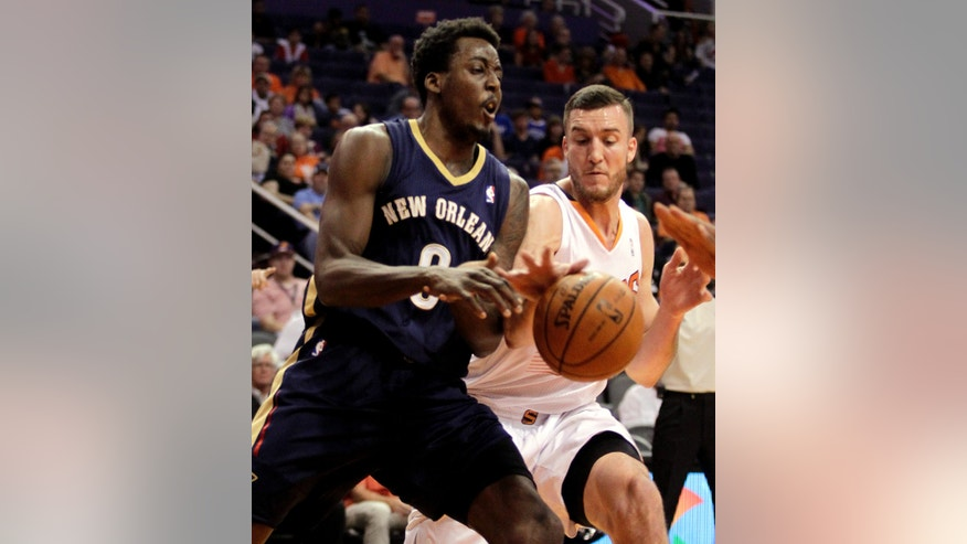 Phoenix Suns center Miles Plumlee (22), right, knocks the ball away from New Orleans Pelicans small forward Al-Farouq Aminu (0) in the first quarter during an NBA basketball game on Sunday, Nov. 10, 2013, in Phoenix. (AP Photo/Rick Scuteri)
