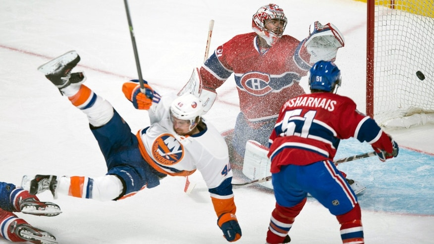 New York Islanders' Michael Grabner is sent flying in front of Montreal Canadiens goalie Carey Price as Canadiens' David Desharnais looks on during third period of an NHL hockey game on Sunday, Nov. 10, 2013, in Montreal. (AP Photo/The Canadian Press, Paul Chiasson)