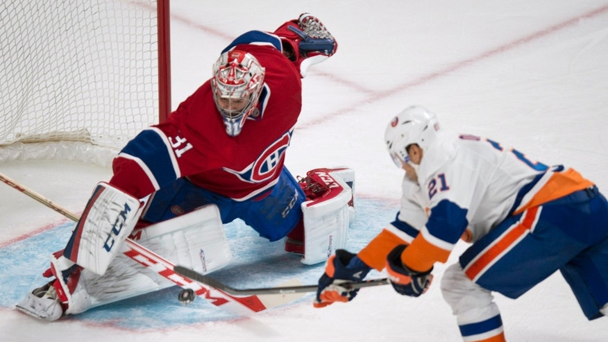 Montreal Canadiens goalie Carey Price makes a save off New York Islanders' Kyle Okposo during the second period of an NHL hockey game on Sunday, Nov. 10, 2013, in Montreal. (AP Photo/The Canadian Press, Paul Chiasson)