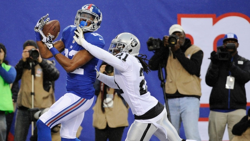 New York Giants wide receiver Rueben Randle, left, catches a touchdown pass as Oakland Raiders cornerback Mike Jenkins (21) defends on the play during the first half of an NFL football game on Sunday, Nov. 10, 2013, in East Rutherford, N.J. (AP Photo/Bill Kostroun)
