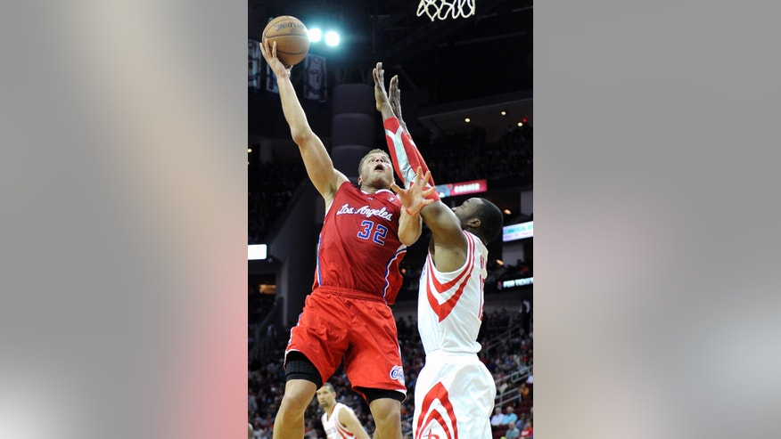 Los Angeles Clippers' Blake Griffin (32) hooks the ball over Houston Rockets' Dwight Howard in the first half of an NBA basketball game on Saturday, Nov. 9, 2013, in Houston. (AP Photo/Pat Sullivan)