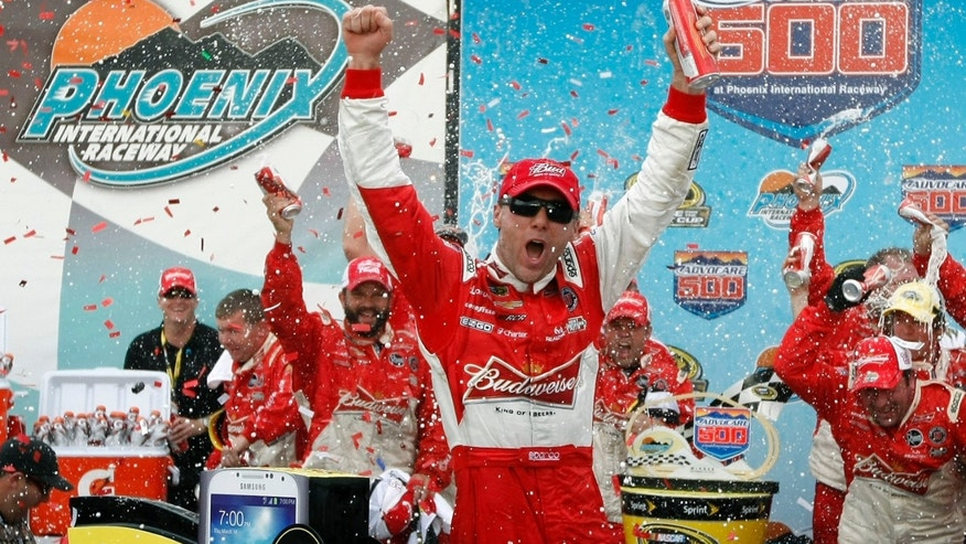 Kevin Harvick, center, celebrates in victory lane after winning the AdvoCare 500 NASCAR Sprint Cup Series auto race at Phoenix International Raceway, Sunday, Nov. 10, 2013, in Avondale, Ariz. (AP Photo/Ralph Freso)