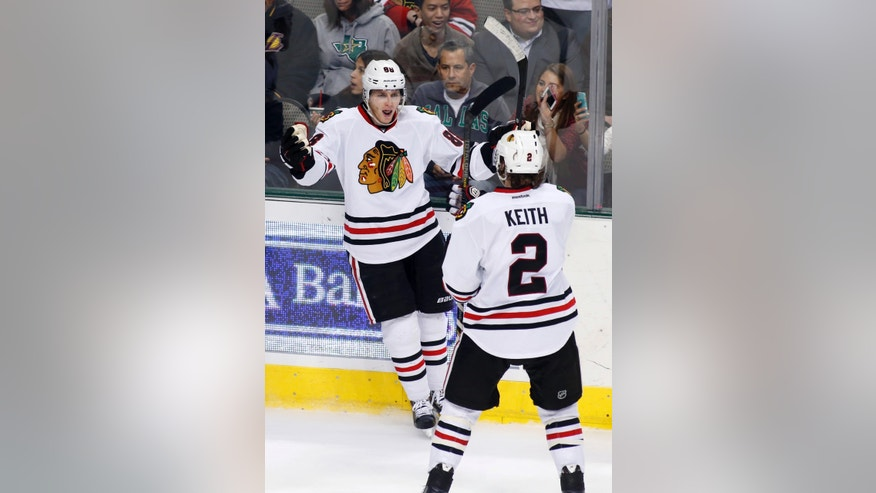 Chicago Blackhawks right wing Patrick Kane, left, celebrates his goal with defenseman Duncan Keith (2) during the second period of an NHL hockey game against the Dallas Stars, Saturday, Nov. 9, 2013, in Dallas, Texas. (AP Photo/Sharon Ellman)
