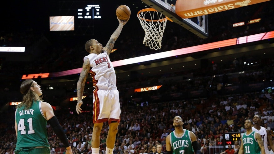 Miami Heat's Michael Beasley (8) shoots as Boston Celtics' Kelly Olynyk (41), Jared Sullinger (7) and Courtney Lee (11) stand by during the first half of an NBA basketball game Saturday, Nov. 9, 2013, in Miami. (AP Photo/Lynne Sladky)