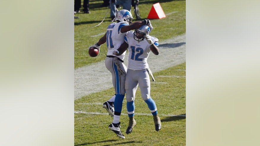 Detroit Lions wide receiver Calvin Johnson (81) celebrates his touchdown catch with teammate Jeremy Ross (12) during the second half of an NFL football game against the Chicago Bears, Sunday, Nov. 10, 2013, in Chicago. (AP Photo/Charles Rex Arbogast)