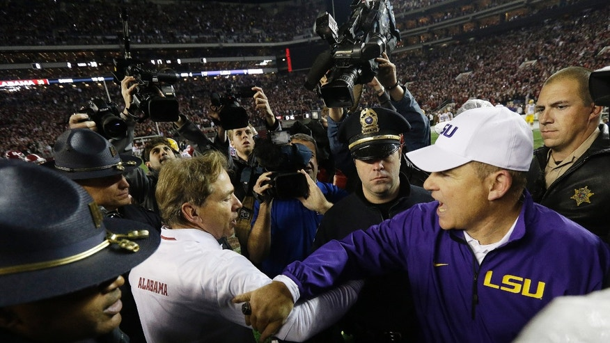 Alabama head coach Nick Saban speaks with LSU head coach Les Miles after the second half of an NCAA college football game, Saturday, Nov. 9, 2013, in Tuscaloosa, Ala. Alabama won 38-17. (AP Photo/Dave Martin)