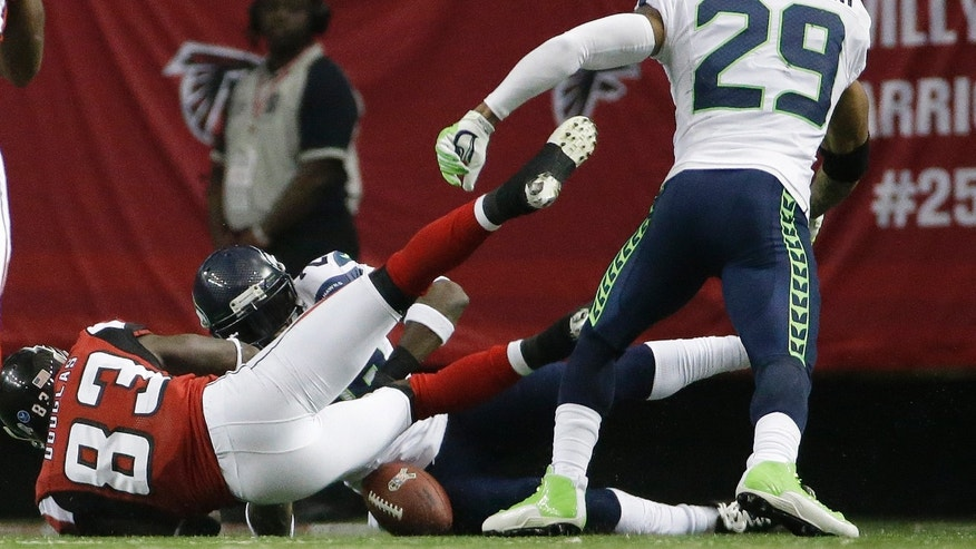 Atlanta Falcons wide receiver Harry Douglas (83) fumbles the ball after a run as Seattle Seahawks cornerback Walter Thurmond (28) recovers the ball during the second half of an NFL football game, Sunday, Nov. 10, 2013, in Atlanta. (AP Photo/David Goldman)