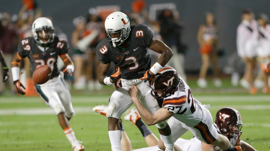 Miami wide receiver Stacy Coley (3) fumbles the ball as he is tackled by Virginia Tech's A.J. Hughes (27) during the first half of an NCAA college football game, Saturday, Nov. 9, 2013, in Miami Gardens, Fla. (AP Photo/Wilfredo Lee)