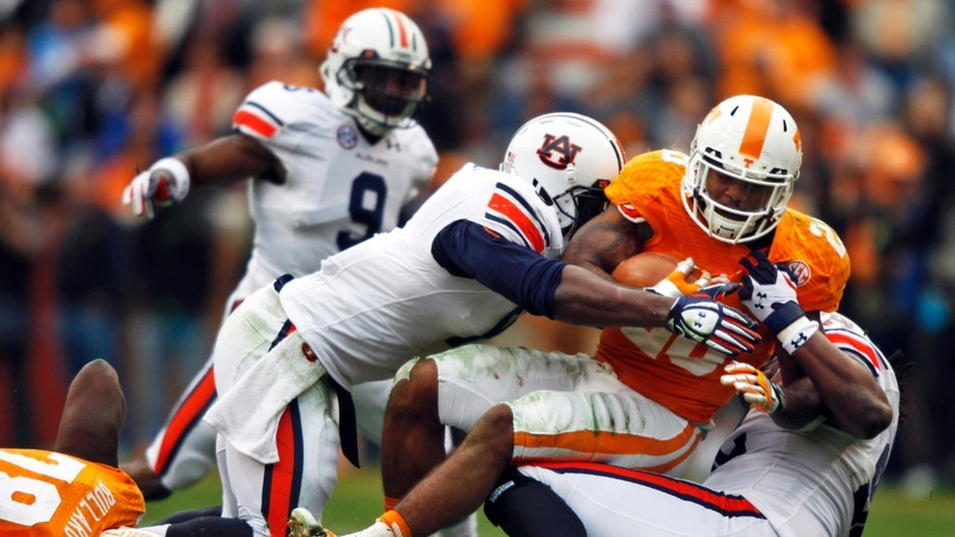 Tennessee running back Rajion Neal (20) is tackled by Auburn linebacker Cassanova McKinzy (8), left, and defensive end Kenneth Carter (92) in the third quarter of an NCAA college football game on Saturday, Nov. 9, 2013 in Knoxville, Tenn. (AP Photo/Wade Payne)