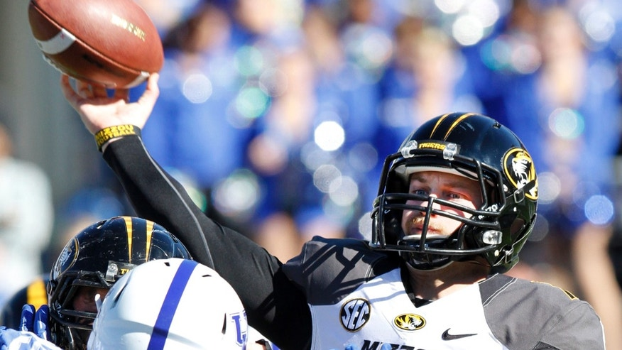 Missouri quarterback Maty Mauk, right, throws under pressure from Kentucky's Donte Rumph (99) during the second quarter of an NCAA college football game, Saturday, Nov. 9, 2013, in Lexington, Ky. (AP Photo/James Crisp)