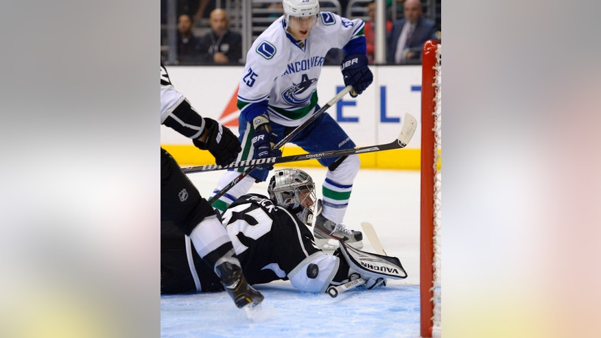 Vancouver Canucks center Mike Santorelli, top, tries to get a shot in on Los Angeles Kings goalie Jonathan Quick during the first period of an NHL hockey game, Saturday, Nov. 9, 2013, in Los Angeles.  (AP Photo/Mark J. Terrill)