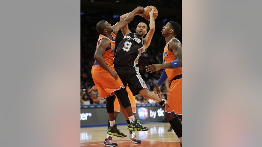 San Antonio Spurs' Tony Parker, center, passes around New York Knicks' defenders Raymond Felton, left, and Iman Shumpert during the first half of the NBA basketball game at Madison Square Garden Sunday, Nov. 10, 2013 in New York. (AP Photo/Seth Wenig)