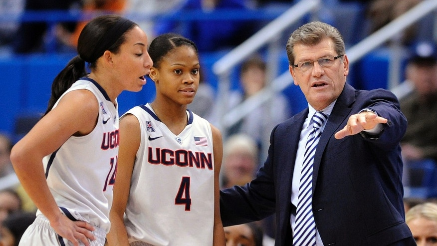Connecticut coach Geno Auriemma speaks with guards Bria Hartley (14) and Connecticut guards Moriah Jefferson (4) during the first half of an NCAA college basketball game against Hartford, in Hartford, Conn., on Saturday, Nov. 9, 2013. Jefferson scored a game-high 17 points in Connecticut's 89-34 victory. (AP Photo/Fred Beckham)