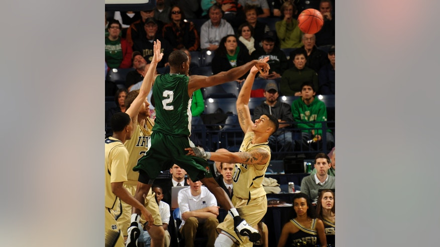 Stetson guard Kentwan Smith (2) passes as Notre Dame forward Zach Auguste, right, and Austin Burgett defend  during the first half of an NCAA college basketball game on Sunday, Nov. 10, 2013, in South Bend, Ind. (AP Photo/Joe Raymond)