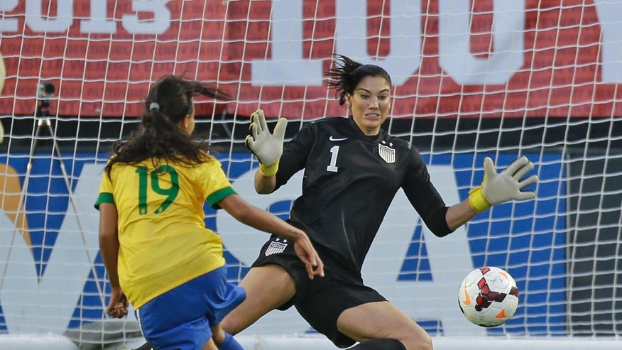U.S. goalkeeper Hope Solo (1) blocks a shot on goal by Brazil forward Raquel (19) during the second half of an international friendly soccer match in Orlando, Fla., Sunday, Nov. 10, 2013. United States Women's national team defeated Brazil 4-1. (AP Photo/John Raoux)
